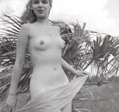 Several sixties beach babes posing naked on a…