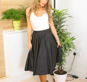 Curly haired blonde in long skirt and satin top