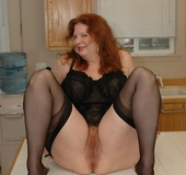 Horny redhead lays on the kitchen table like shes…